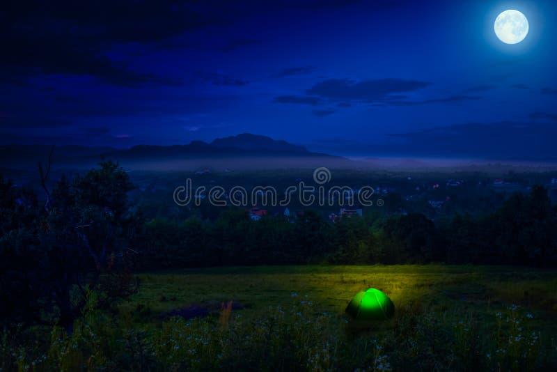 Turista que acampa perto da floresta na noite Barraca iluminada sob o céu noturno bonito completo das estrelas e da Lua cheia Cam foto de stock