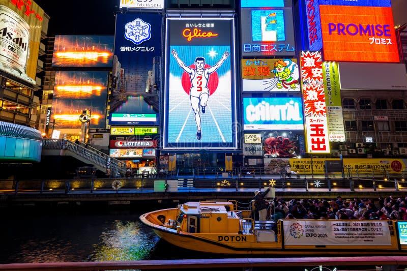 Turista que anda na rua da compra da noite em Dotonbori em Osaka, Japão foto de stock royalty free