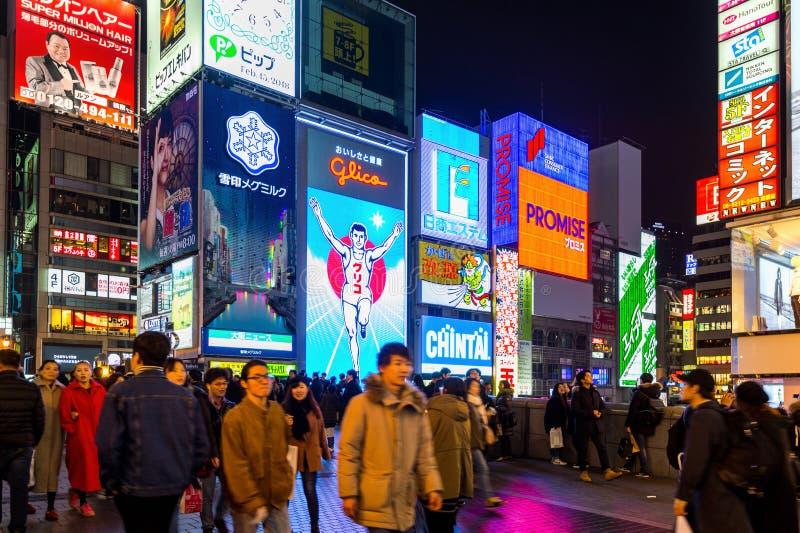 Turista que anda na rua da compra da noite em Dotonbori em Osaka, Japão fotografia de stock