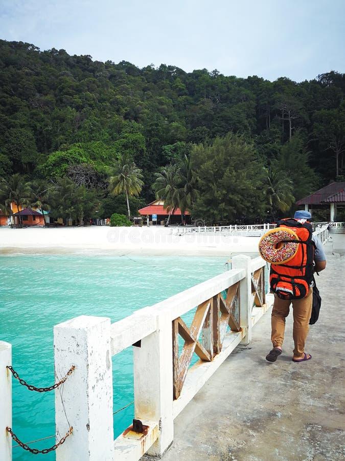 Turista que anda no molhe que vai o à ilha em cima da chegada fotografia de stock royalty free