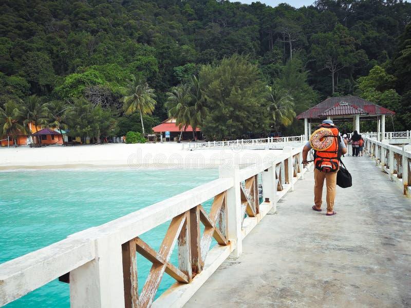 Turista que anda no molhe que vai o à ilha em cima da chegada fotografia de stock