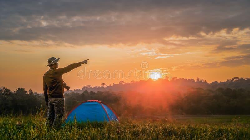 Turista que apontando o dedo tenha um acampamento com a barraca no campo de grama imagem de stock royalty free