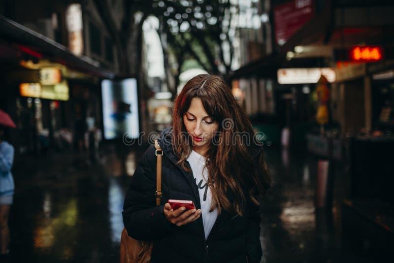 Turista que busca para el restaurante con el teléfono móvil en Chinatown, Sydney fotos de archivo