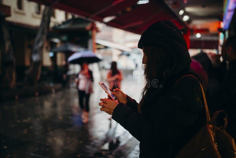 Turista que busca para el restaurante con el teléfono móvil en la vecindad de Chinatown, Sydney, Australia foto de archivo libre de regalías