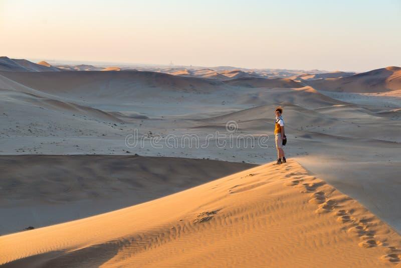 Turista que camina en la duna escénica 7 en la bahía de Walvis, desierto de Namib, parque nacional de Namib Naukluft, Namibia Luz imagen de archivo