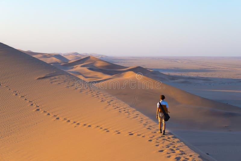 Turista que camina en las dunas escénicas de Sossusvlei, desierto de Namib, parque nacional de Namib Naukluft, Namibia Luz de la  foto de archivo libre de regalías