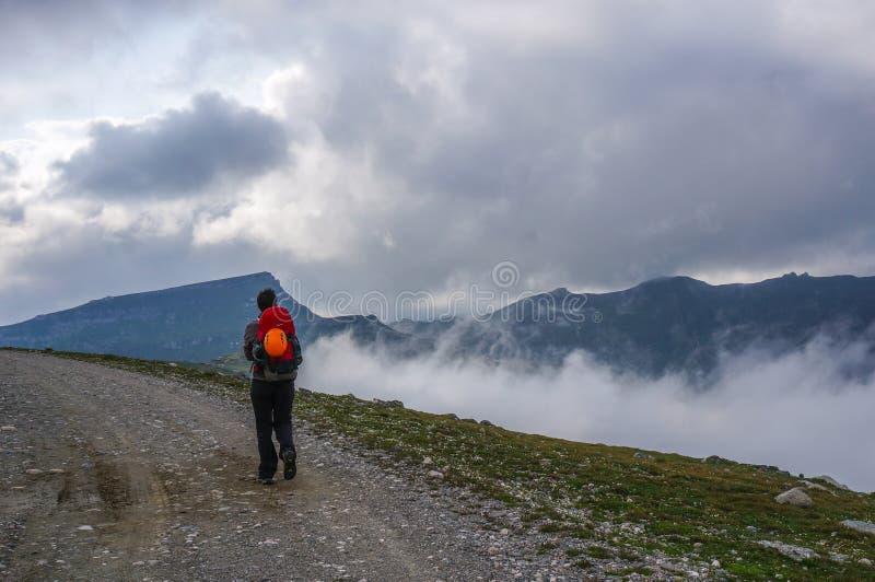 Turista que caminha em um trajeto alto nas montanhas. foto de stock royalty free
