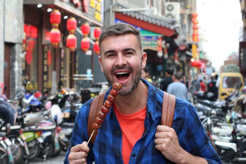 Turista que come Bing Tanghulu Candied Hawthorn Stick foto de stock