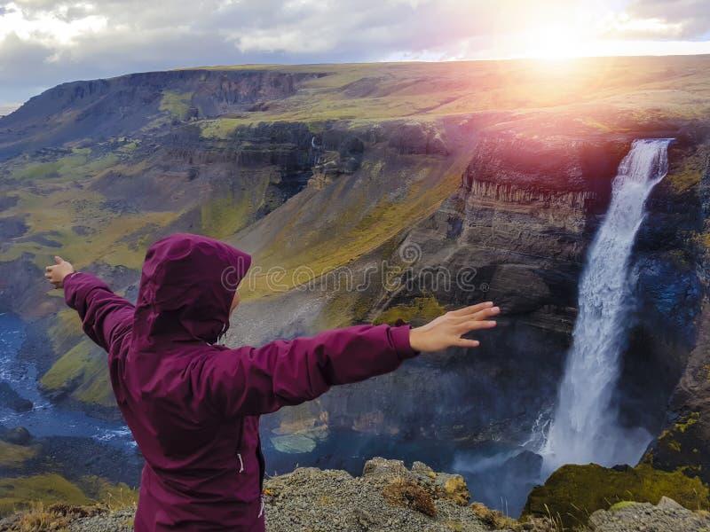 Turista que disfruta de vista dramática de la alta cascada en Islandia fotos de archivo