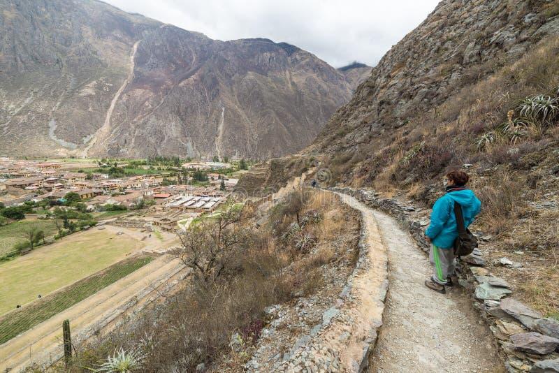 Turista que explora Inca Trails y el sitio arqueológico en Ollantaytambo, valle sagrado, destino del viaje en la región de Cusco, imagen de archivo libre de regalías