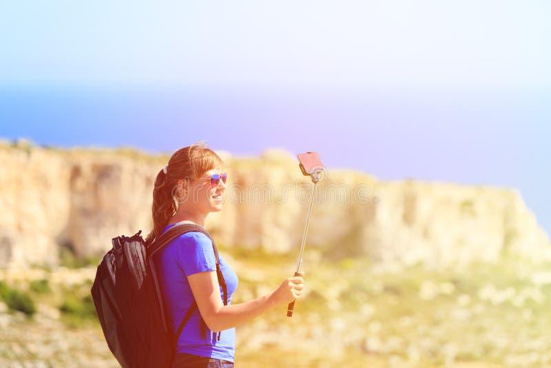 Turista que faz a foto do selfie no curso das montanhas fotografia de stock