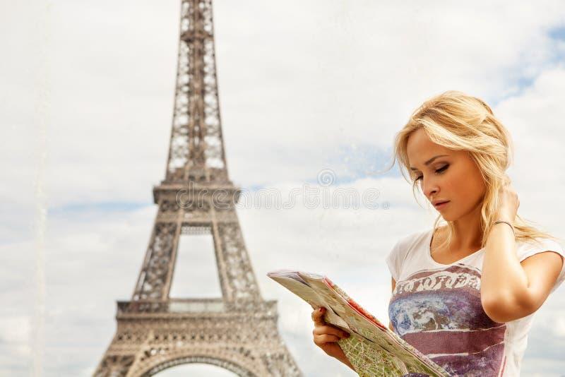Turista que olha o mapa da cidade Paris perto da torre Eiffel, excursão imagem de stock royalty free