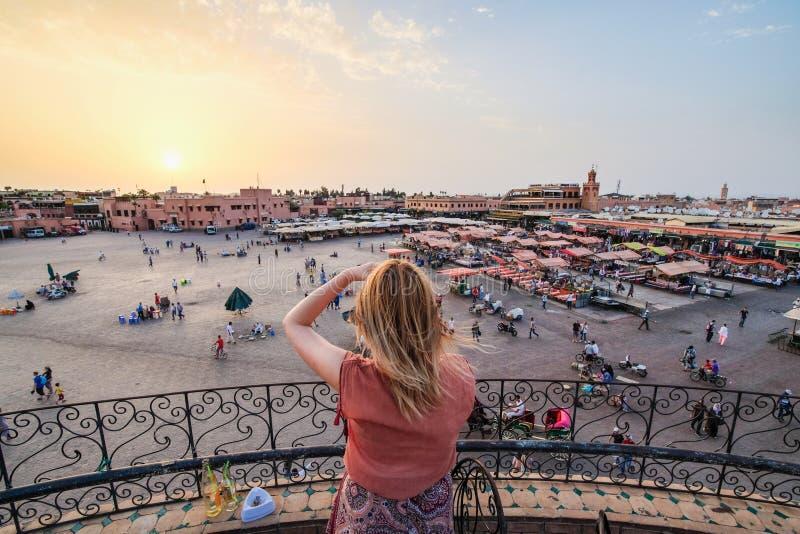 Turista que olha sobre o mercado C4marraquexe - Marrocos do EL-Fna de Jamaa S imagens de stock royalty free