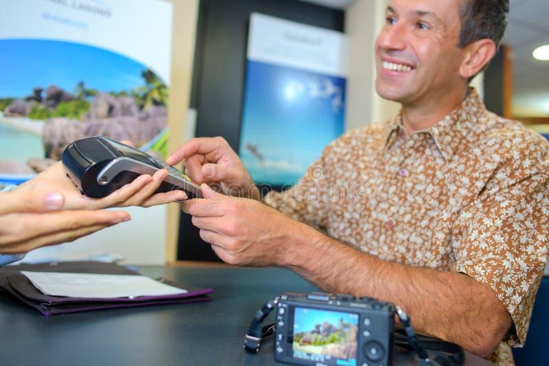 Turista que paga o agente traval pelo cartão de crédito fotografia de stock