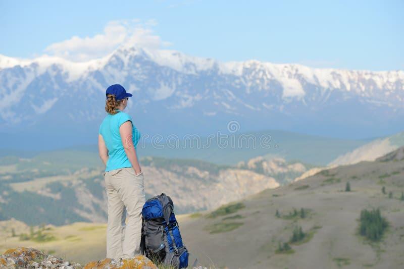 Turista que se coloca en un acantilado que mira las montañas imagen de archivo