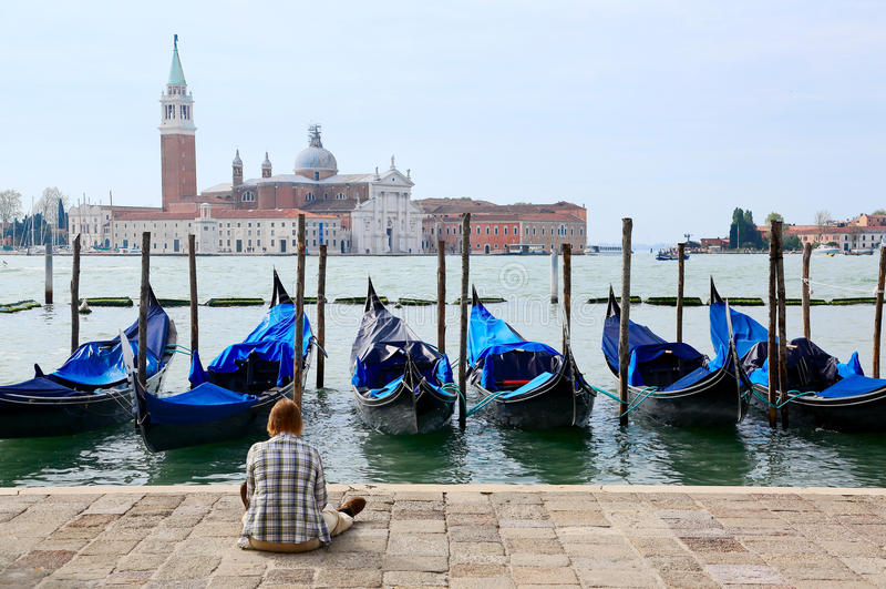 Turista que senta-se em San Marco Square em Veneza, apreciando a vista das gôndola em Grand Canal e em San Giorgio Maggiore Churc imagens de stock