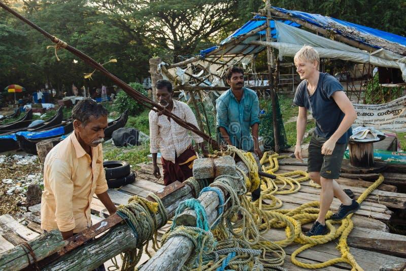 Turista que tenta a vida indiana do ` s dos pescadores sobre em Kochi fotos de stock royalty free