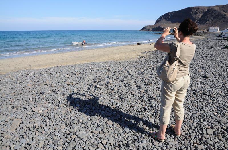 Turista que toma cuadros de una playa hermosa foto de archivo libre de regalías