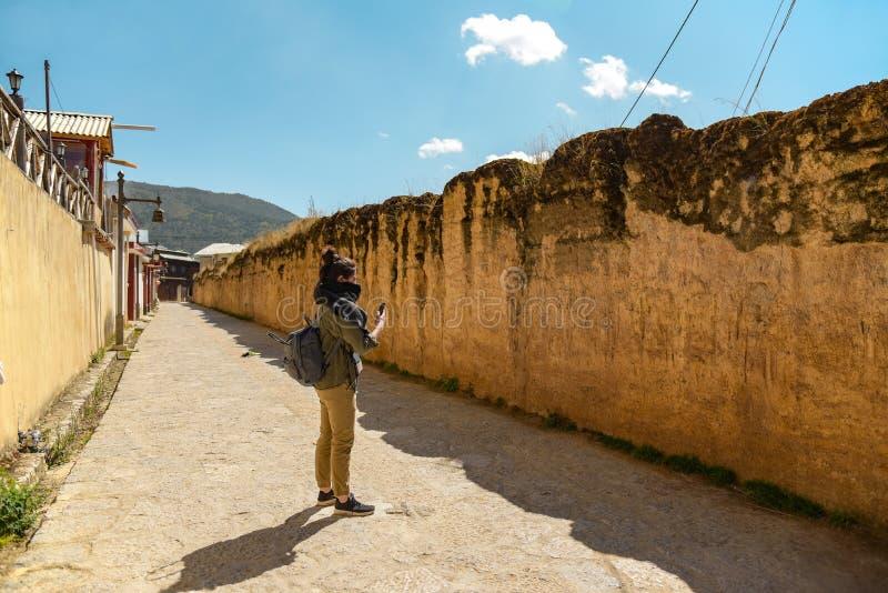 Turista que toma a fotos la pared vieja en la ciudad antigua de Dukezong imagen de archivo libre de regalías