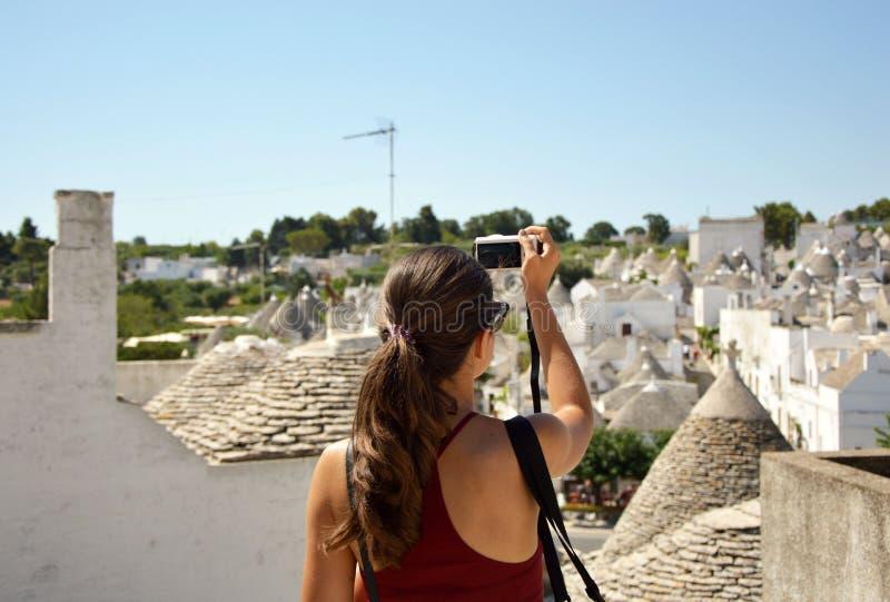 Turista que toma a imagem do curso com a câmera mirrorless da arquitetura da cidade do trulli de Alberobello durante férias de ve imagens de stock