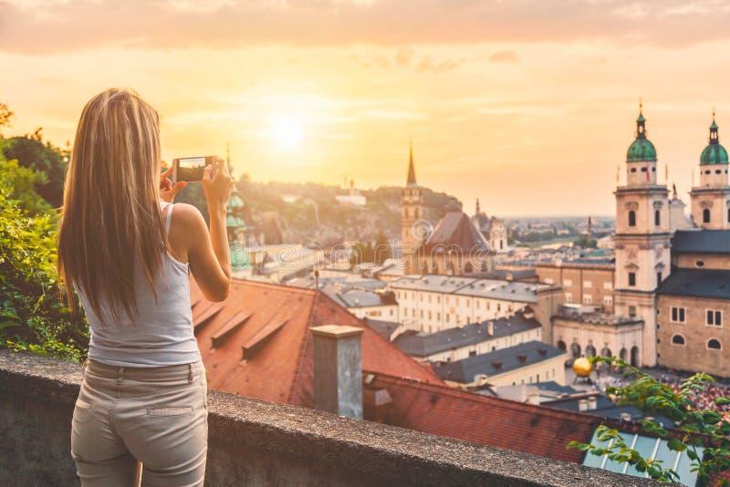 Turista que toma uma foto do por do sol bonito em Salzburg Áustria imagem de stock