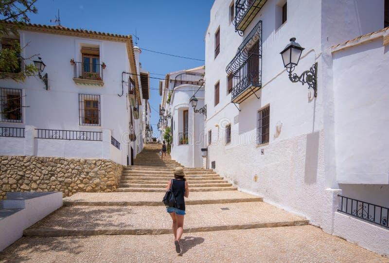 Turista que va para arriba una escalera coblestoned en Altea, España foto de archivo