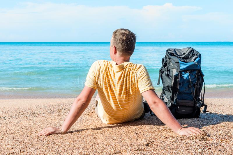 Turista relajado con una mochila cerca del mar imagenes de archivo
