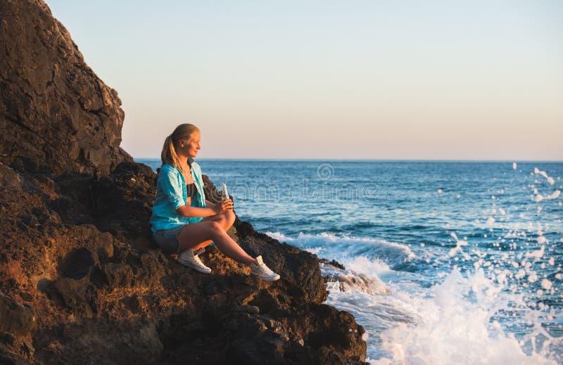 Turista rubio joven de la mujer con la botella de cristal de sittig de la limonada en rocas por el mar en la puesta del sol Alany imagen de archivo libre de regalías