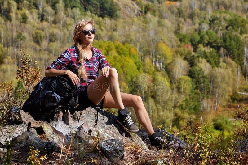 Turista rubio joven de la mujer con la mochila que se sienta en un acantilado encendido foto de archivo libre de regalías