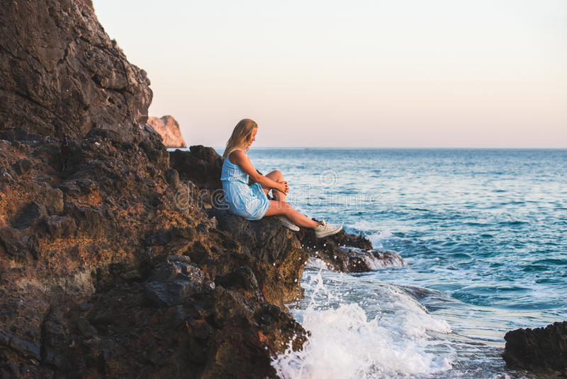 Turista rubio joven de la mujer en el vestido azul que se relaja en las rocas de piedra por el mar ondulado en la puesta del sol  imagenes de archivo