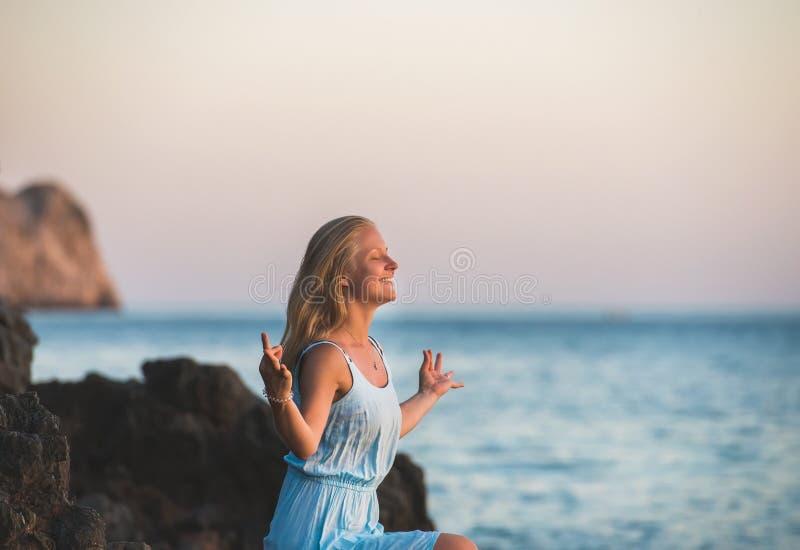 Turista rubio joven de la mujer en el vestido azul que se relaja, meditando y sonriendo en las rocas de piedra por el mar ondulad fotos de archivo