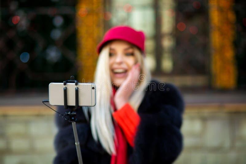 Turista rubio sorprendido de la muchacha que lleva el sombrero divertido, tomando el selfie imagenes de archivo