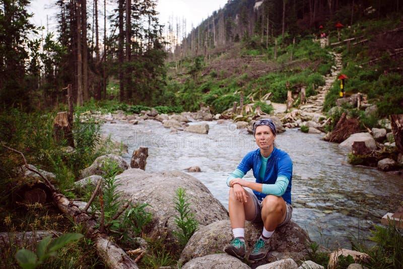 Turista Sedin de la muchacha en la piedra cerca del río de la montaña en alto Tatras en Eslovaquia Vestido en una camiseta azul,  imagen de archivo