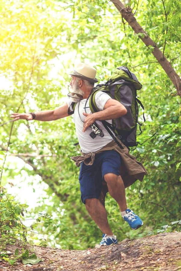 Turista senior terrorizzato che sfugge da qualcosa in terreno boscoso immagine stock libera da diritti