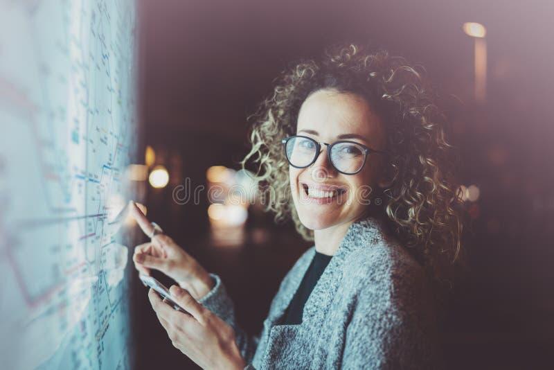 Turista sonriente de la mujer de moda con los vidrios de los ojos que miran en smartphone mientras que comprueba manera en el map fotos de archivo libres de regalías