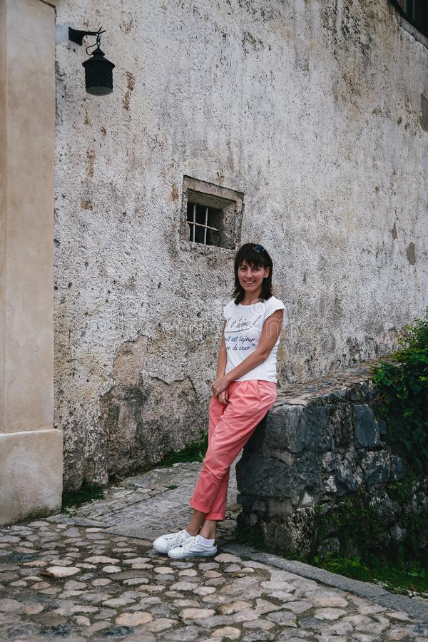 Turista sonriente joven de la mujer que se sienta en una pared sangrada del castillo en el patio Camisa blanca que lleva, zapatil fotografía de archivo