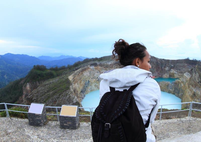 Turista su Kelimutu che guarda il rubinetto e la latta unici dei laghi immagine stock