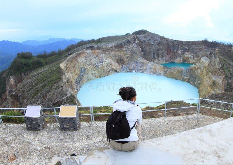 Turista su Kelimutu che guarda il rubinetto e la latta unici dei laghi fotografia stock
