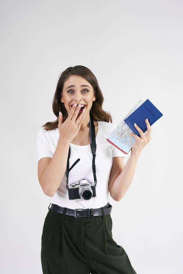 Turista surpreendido com câmera, mapa e passaporte no tiro do estúdio fotografia de stock