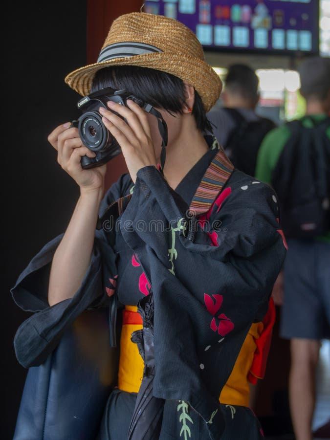 Turista vestito in kimono che prende una foto immagine stock libera da diritti