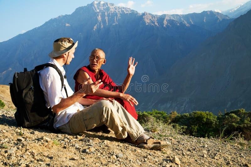 Turista y monje en montañas fotos de archivo