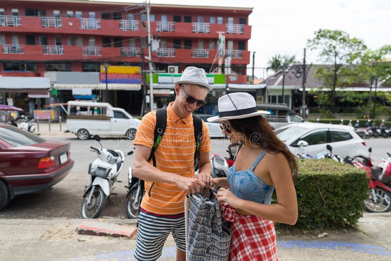 Turistas alegres del hombre y de la mujer de la calle de la ciudad de los pares que caminan jovenes con las mochilas que exploran foto de archivo libre de regalías