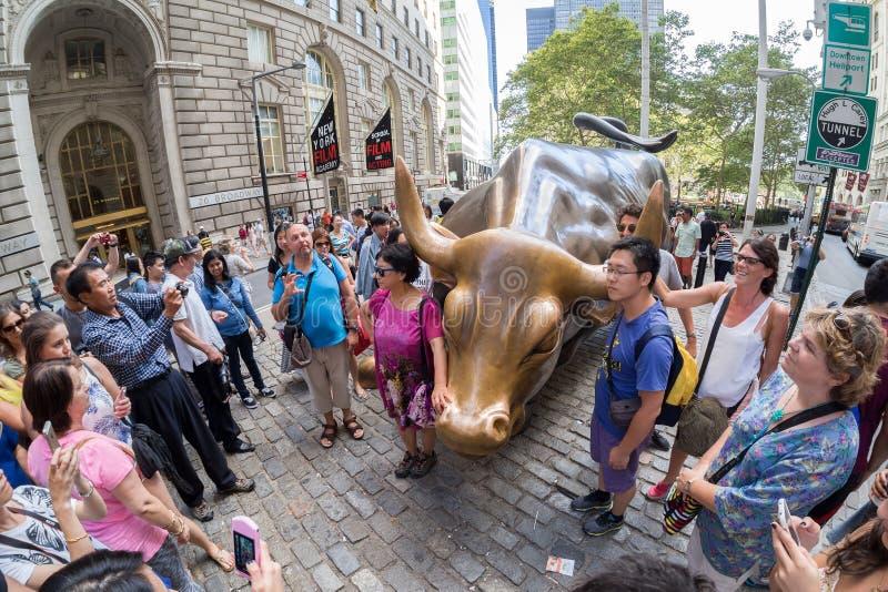Turistas ao lado da escultura de Wall Street Bull em New York City imagens de stock