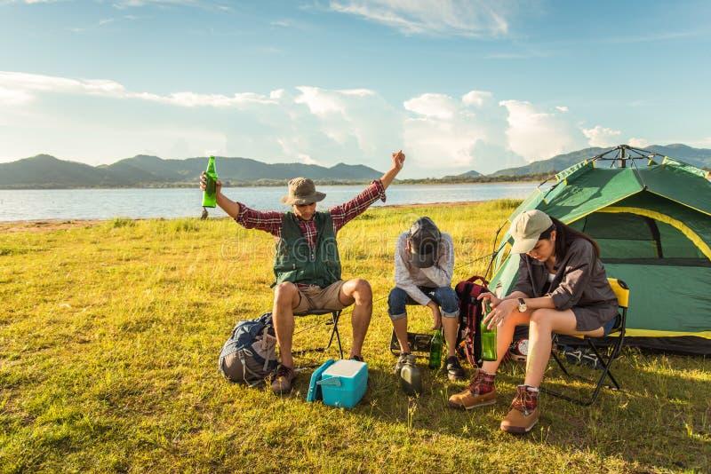 Turistas bêbados que fazem o partido ao acampar e ao piquenique no prado fotos de stock royalty free