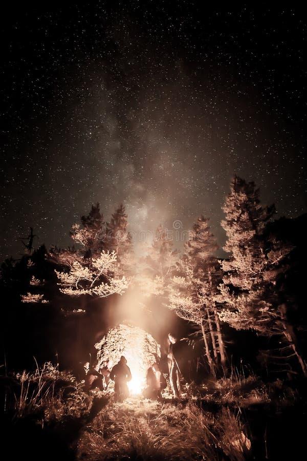 Turistas cerca de un fuego bajo las estrellas imagen de archivo libre de regalías