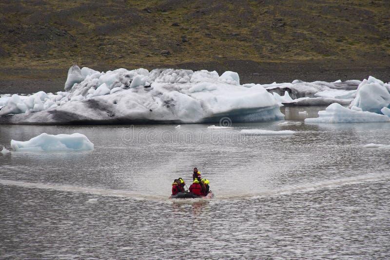 Turistas cerca del hielo congelado del glaciar en Islandia foto de archivo