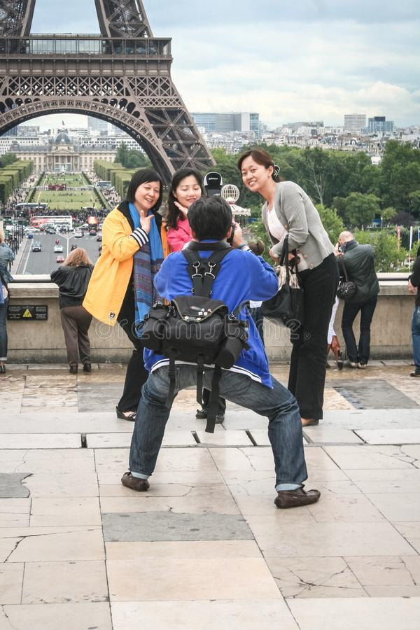 Turistas chineses que tomam fotos na frente da torre Eiffel A excursão Eiffel é uma das atrações principais de Paris fotos de stock royalty free