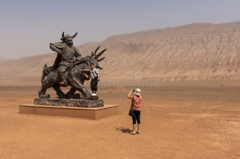 Turistas chineses que tomam imagens na frente de uma estátua perto das montanhas flamejantes, Xinjiang imagem de stock