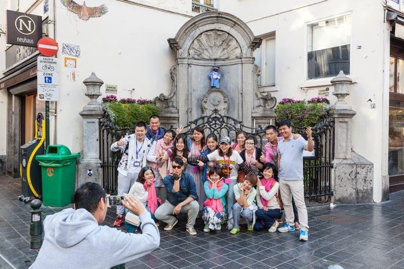 Turistas chinos en la estatua de Manneken Pis en Bruselas fotografía de archivo