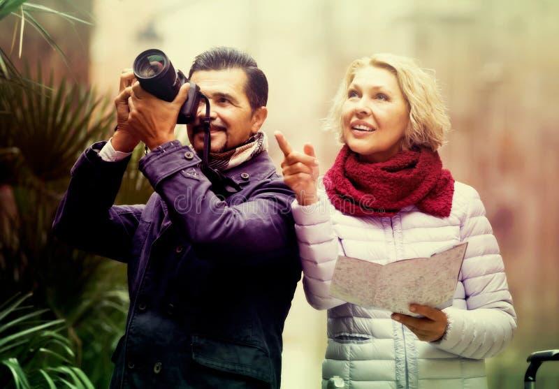 Turistas con el mapa y el equipaje en la calle de la ciudad imágenes de archivo libres de regalías